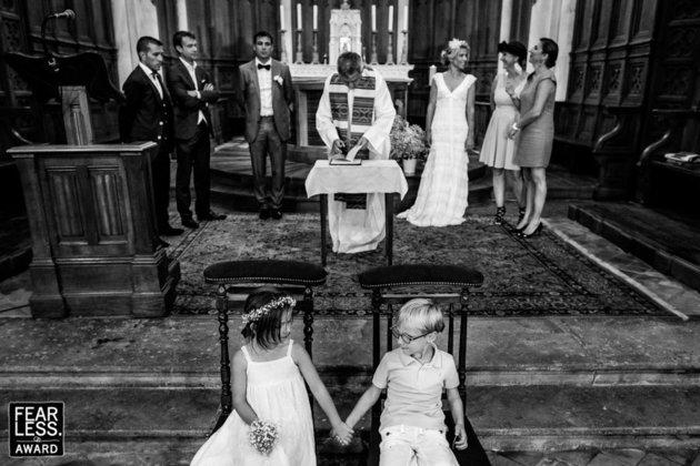 Deux enfants assis sur les prie Dieu se regardent et se prennent la main